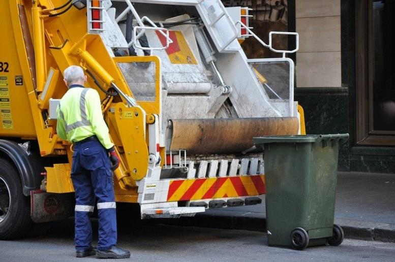 Рабочий возле мусорной машины