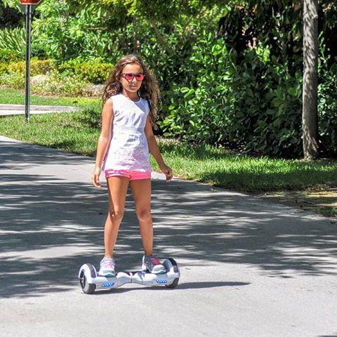 Маленькая девочка на гироскутере летом в парке