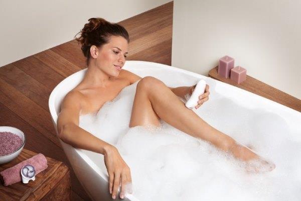 Девушка в ванне с эпилятором