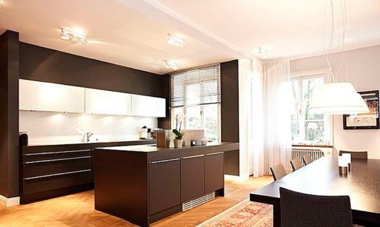 Темно-шоколадная кухня и гостиная в светло-древесных тонах