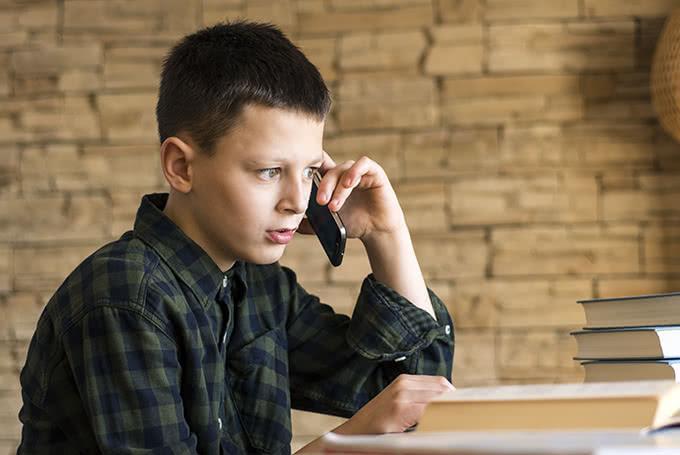 Школьник разговаривает по смартфону