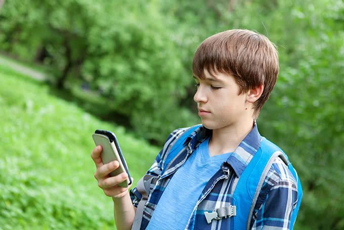 Школьник на улице со смартфоном