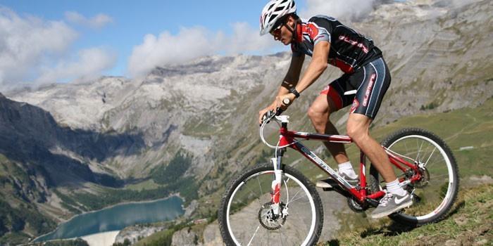 Мужчина ездит по горной местности на велосипеде