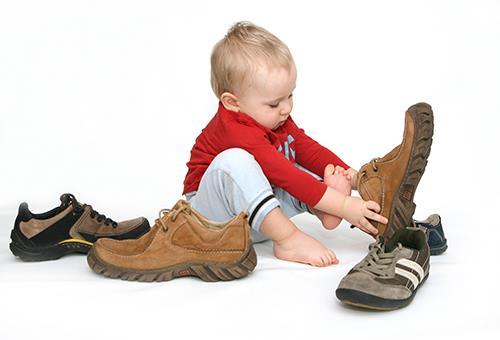 Ребенок примеряет обувь взрослых