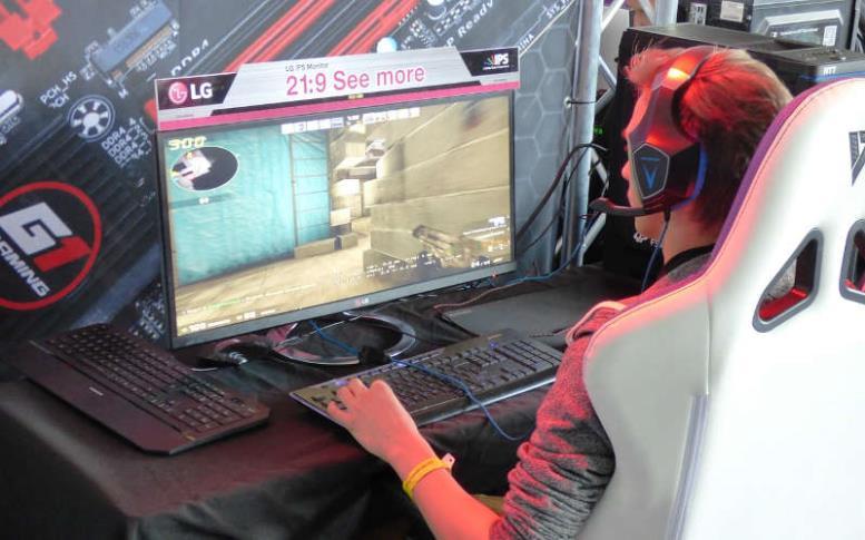 Мужчина играет в компьютерную игру в наушниках