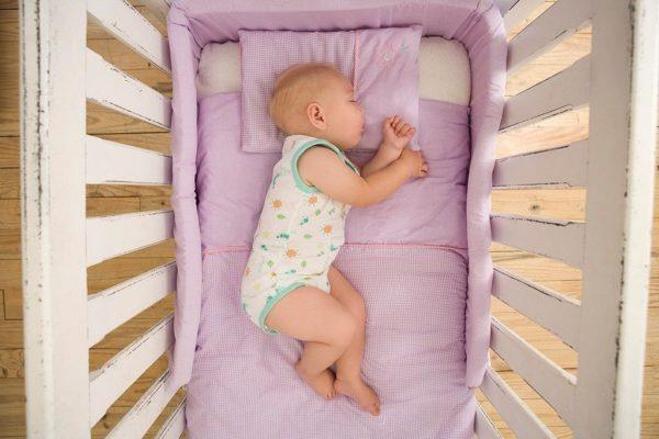 Новорожденный спит на матрасе.